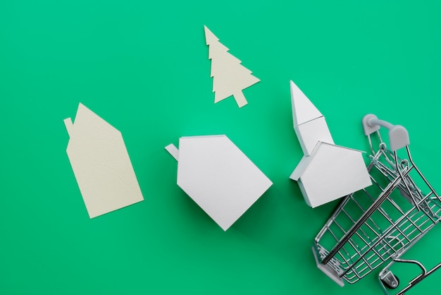 Different type of paper houses; tree falling from the shopping trolley over green background