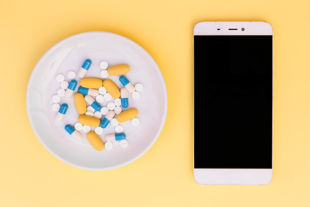 Different type of pills on white plate near the smartphone on yellow background