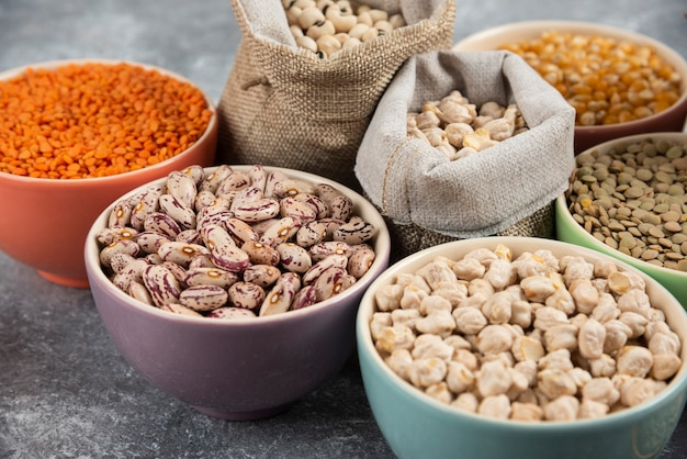 Different type of raw dry legumes composition on marble table surface.