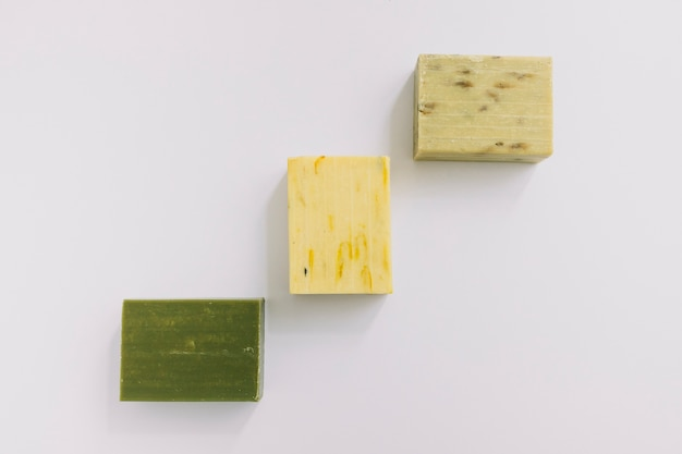 Different type of soaps on white backdrop