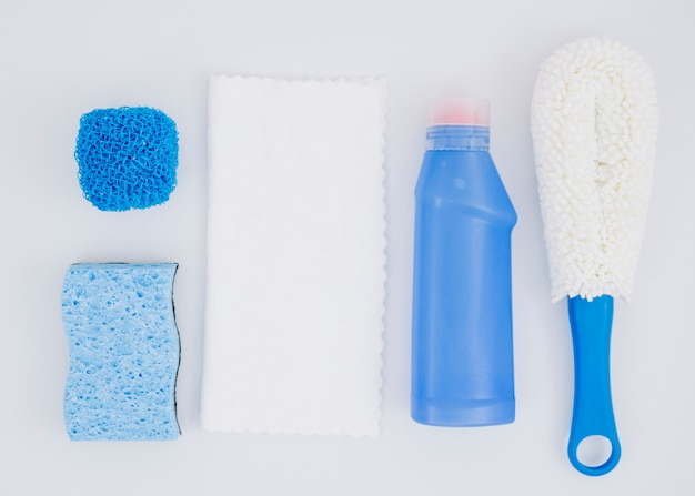 Different type of sponges with blue detergent bottle on white backdrop