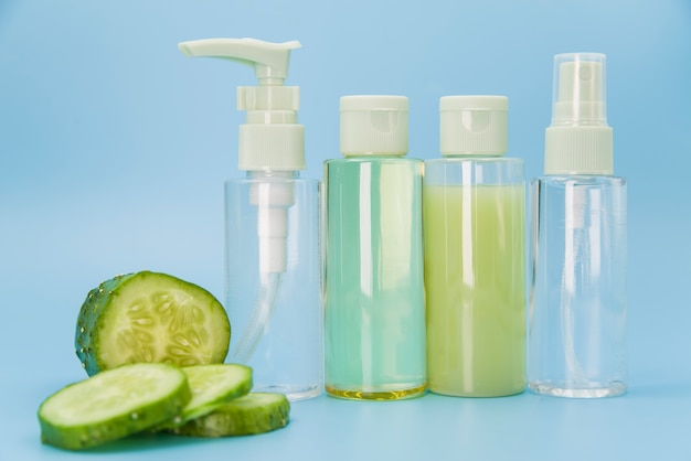 Different type of spray bottles with cucumber slices on blue background