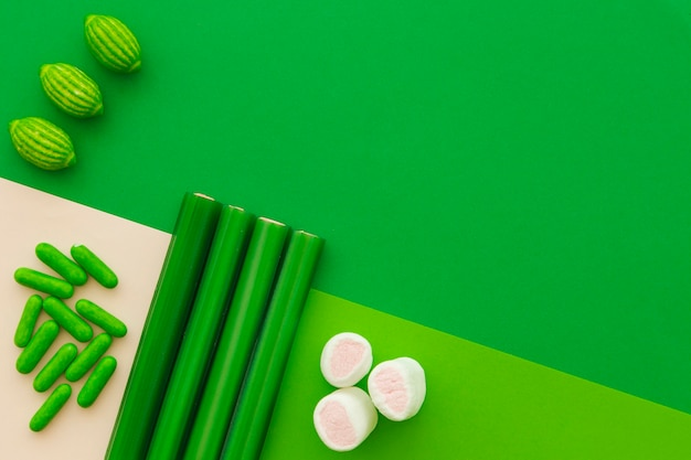 Different type of sweet candies on green background