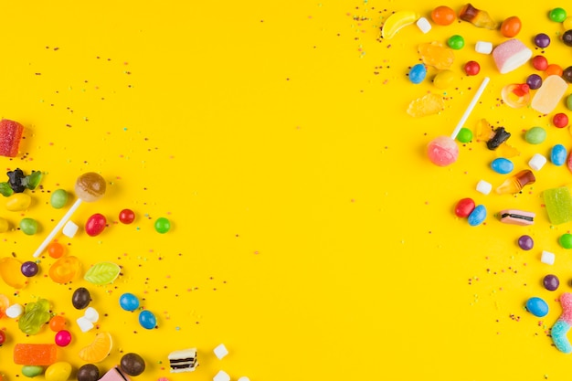 Different type of sweet candies on yellow surface
