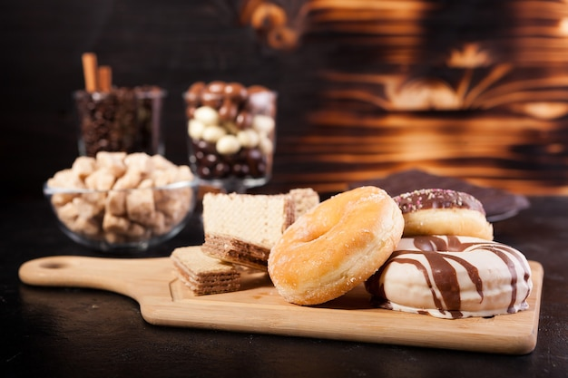 Different type of sweets on wooden board and background