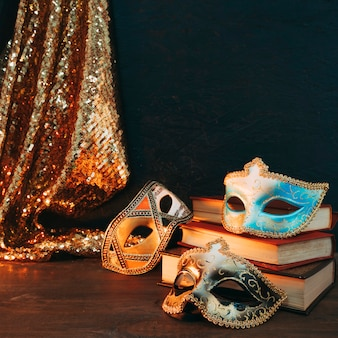 Different type of three carnival mask on stack of books with glitter sequins fabric over wooden desk