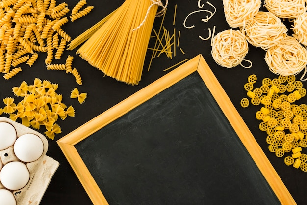 Different type of uncooked pasta with eggs and blackboard on black background