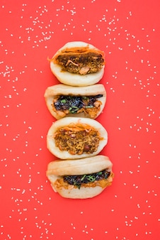 Different types of asian sandwich steamed gua bao buns surrounded with white sesame seeds on red background