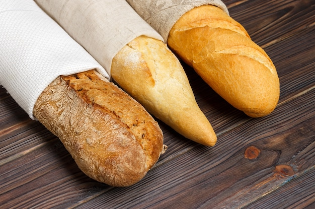 Different types of baguette on wood