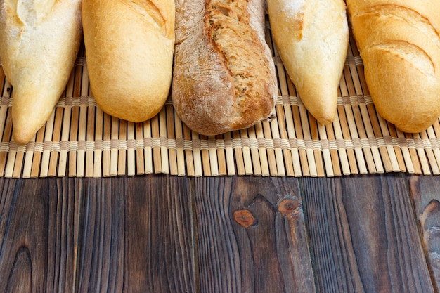 Different types of baguette on a wooden background