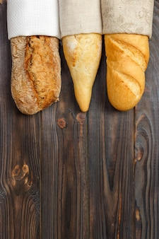 Different types of baguette on a wooden surface