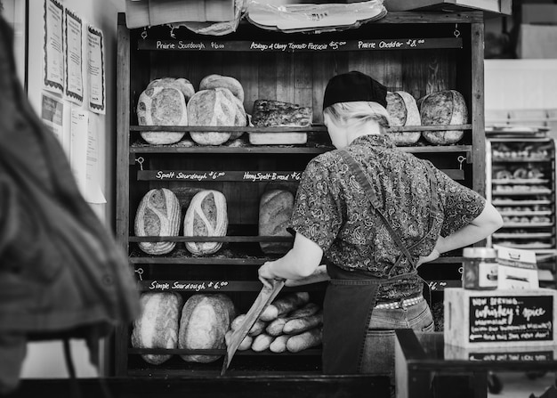 Different types of bread on bakery shelves, baker woman