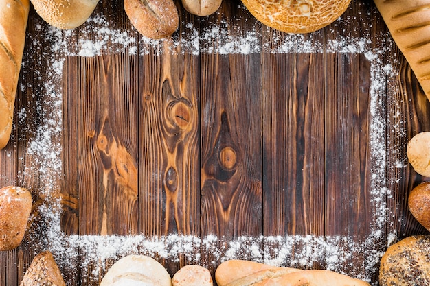 Different types of bread spread at the edge of flour on wooden table