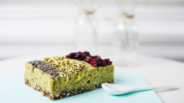 Different types of cake slice with chia; pistachios and dried cranberries toppings on chopping board