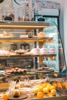Different types of cakes and sweets in pastry shop glass display