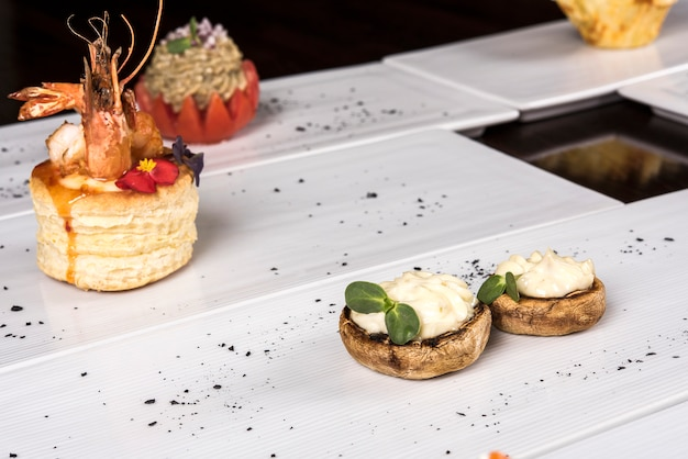 Different types of canapes,  placed on individual plates,  finger food,  dark background