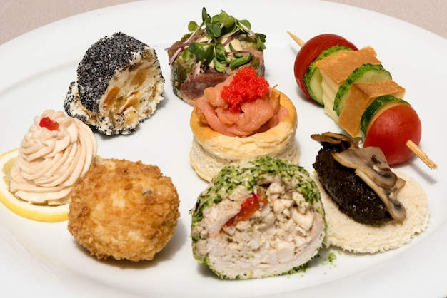 Different types of canapes, placed on white plates, finger food