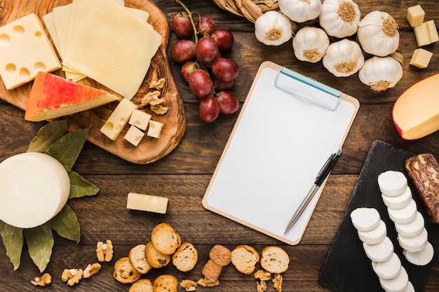 Different types of cheese and blank clipboard on table