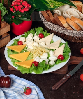 Different types of cheese located on a wooden board and decorated with cherry tomatoes, lettuce and fresh bread.