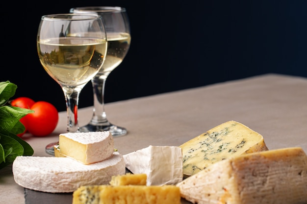Different types of cheese and wine on gray table