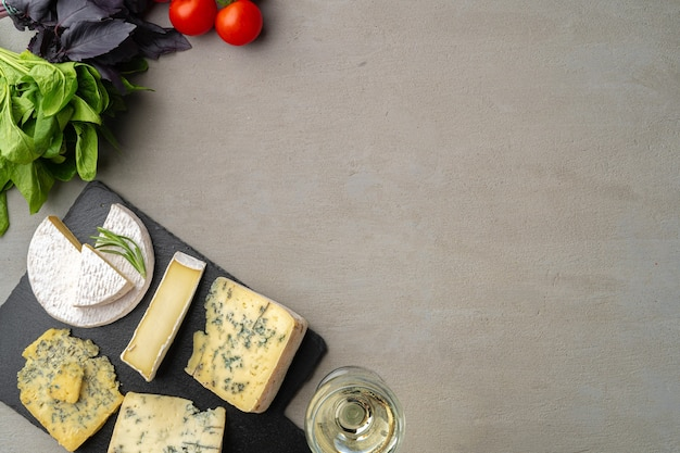 Different types of cheese and wine served on gray table