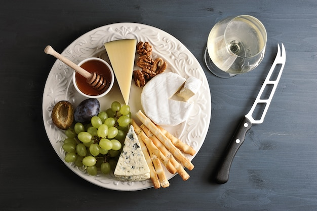 Different types of cheese with mildew, grapes honey and nuts on a plate, a glass of wine