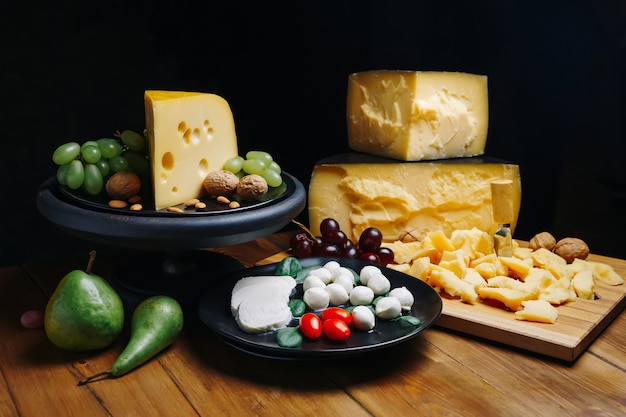Different types of cheese with walnuts and grapes on rustic wooden background