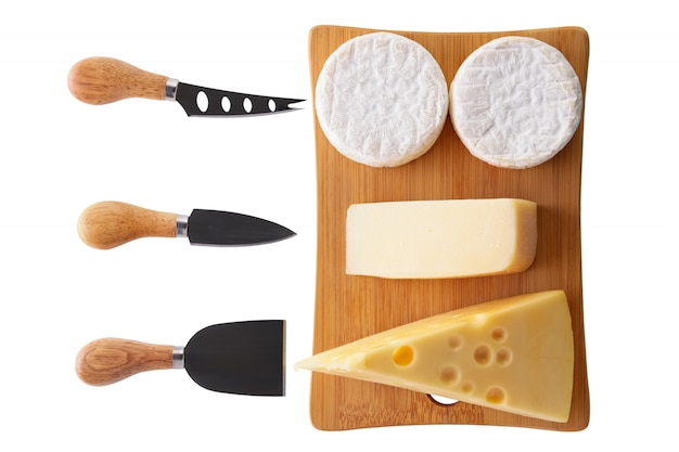 Different types of cheeses - brie, camembert, parmesan and gouda on wooden board with cheese knives isolated on white