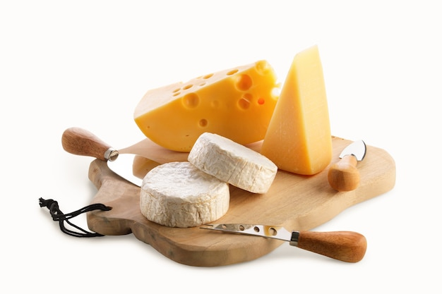 Different types of cheeses - brie, camembert, parmesan and gouda on wooden board with cheese knives