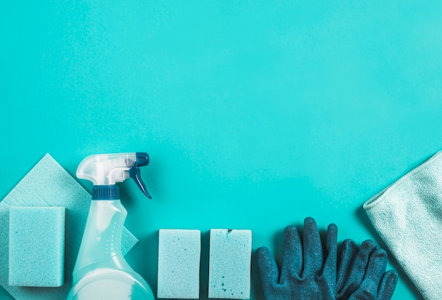 Different types of cleaning items on turquoise background