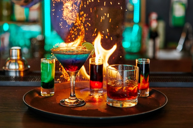 Different types of cocktails on fire in bar with lime, alcohol, bar