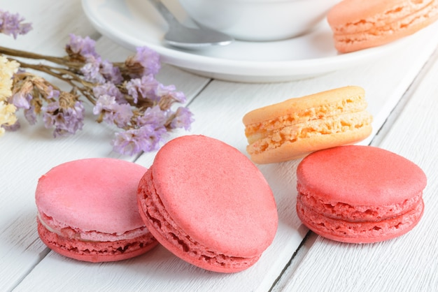 Different types color of macaroons with cup of hot tea on white wood