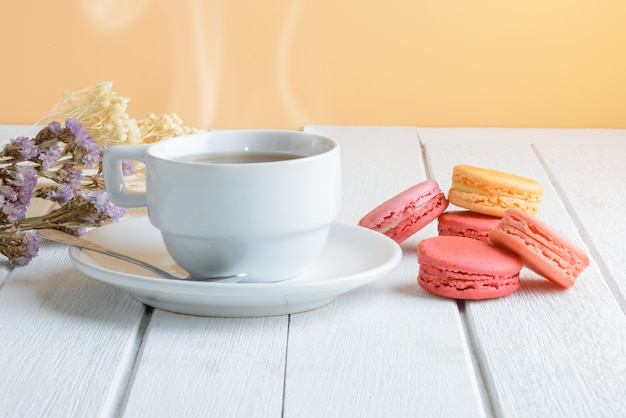 Different types color of macaroons with cup of hot tea on white wooden surface