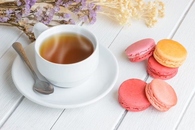 Different types color of macaroons with cup of hot tea