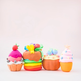 Different types of colorful cakes made with clay on pink background