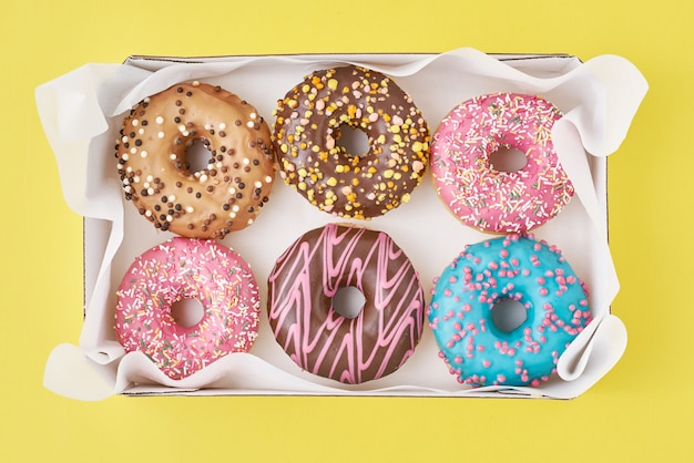 Different types of colorful donats decorated sprinkles and icing in box on yellow, top view