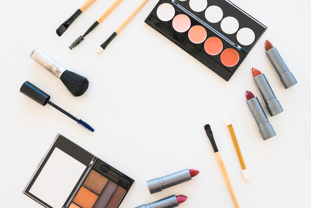 Different types of colorful makeup palette; lipstick; mascara; brush on white backdrop