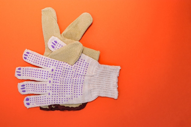 Different types of construction gloves on a bright orange background. means of protection and security. copy space for text.