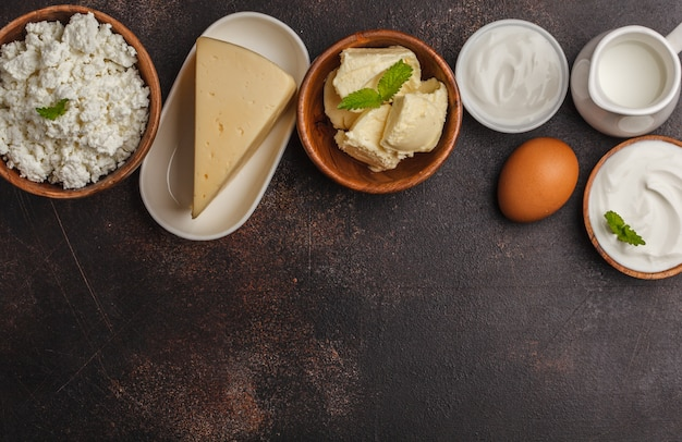 Different types of dairy products on dark background, top view, copy space.