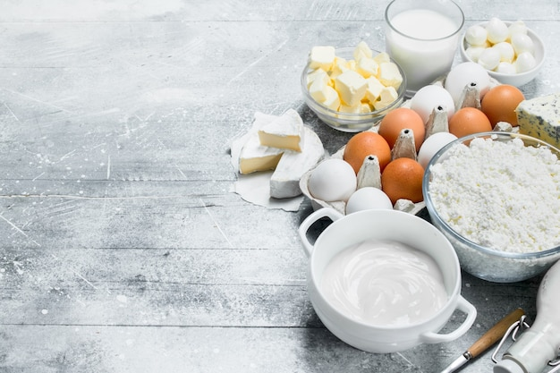 Different types of dairy products on rustic table.