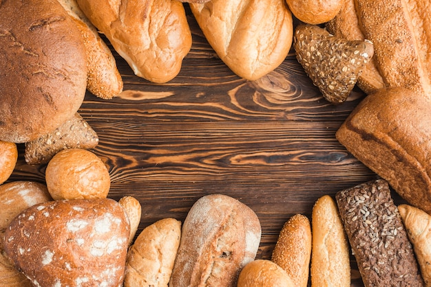 Different types of delicious breads on wooden desk