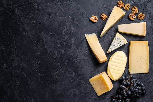 Different types of delicious cheese. black background. top view. space for text