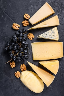 Different types of delicious cheese with walnuts and grapes. black background. top view