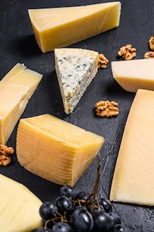 Different types of delicious cheese with walnuts and grapes. top view
