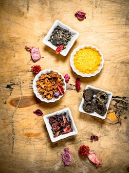 Different types of dried tea in the cups . on wooden table.