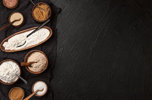 Different types of flour in wooden bowls on black table, top view of flour and rolling pin with copy space