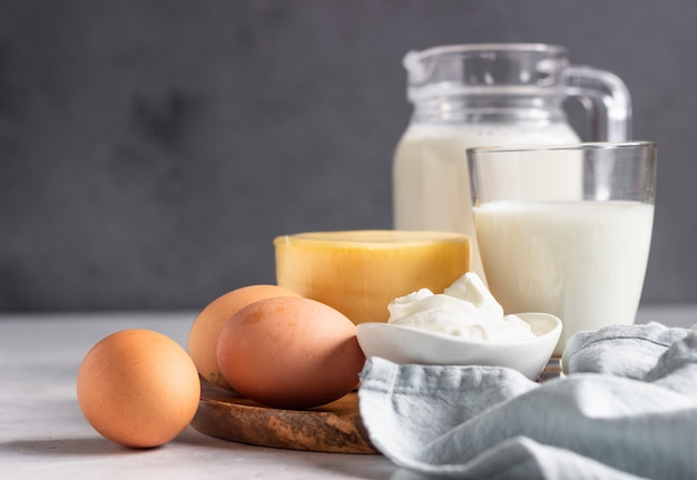 Different types of fresh dairy products and eggs on wooden plate. natural farm products.