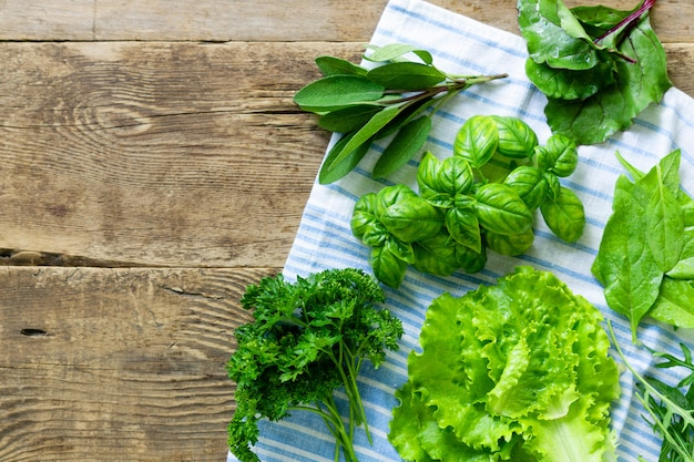 Different types of fresh herbs on old wooden background