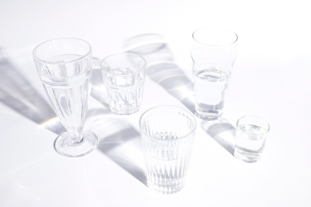 Different types of glasses with shadow on white backdrop