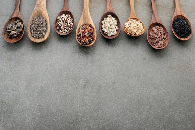 Different types of grains and cereals on shabby concrete background.